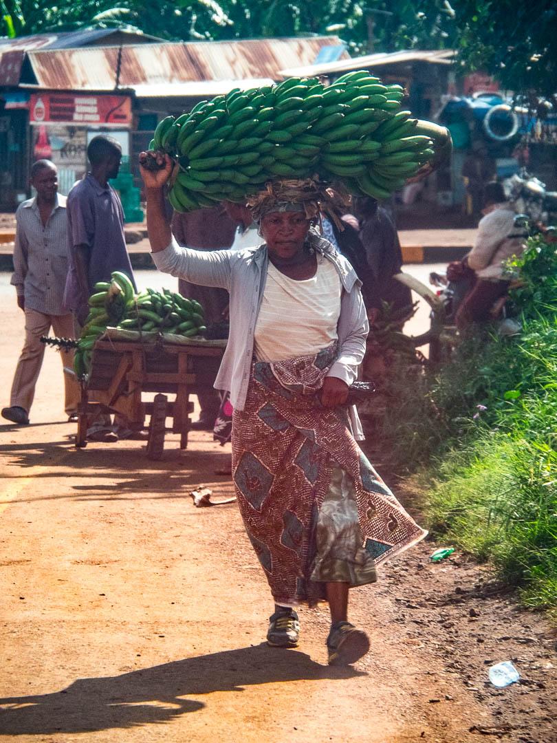 Woman brining bananas to a market in Mwika Tanzania