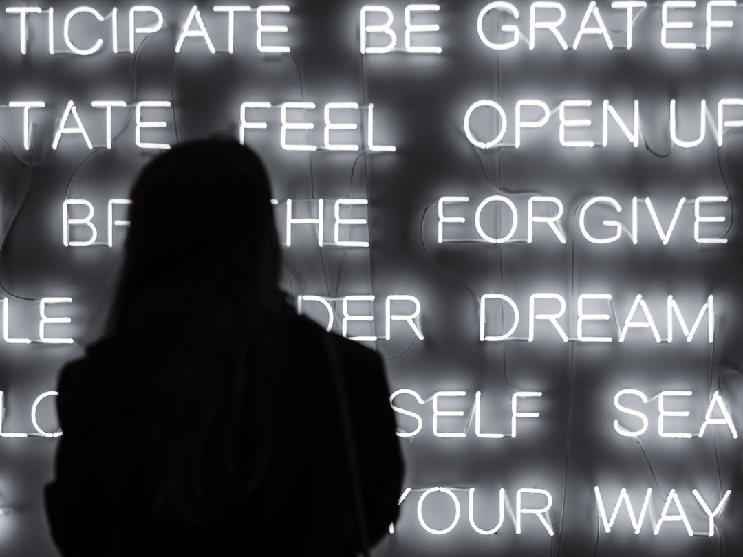 Photograph of a Silhouette of a girl in front of lighted buzz words