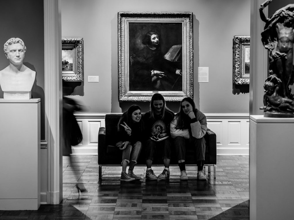 Four girls visiting an art museum sitting in front of paintings
