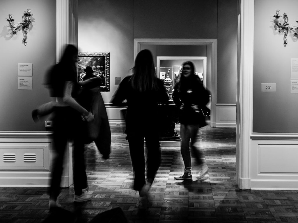 Blurred silhouettes of 4 girls visiting an art museum