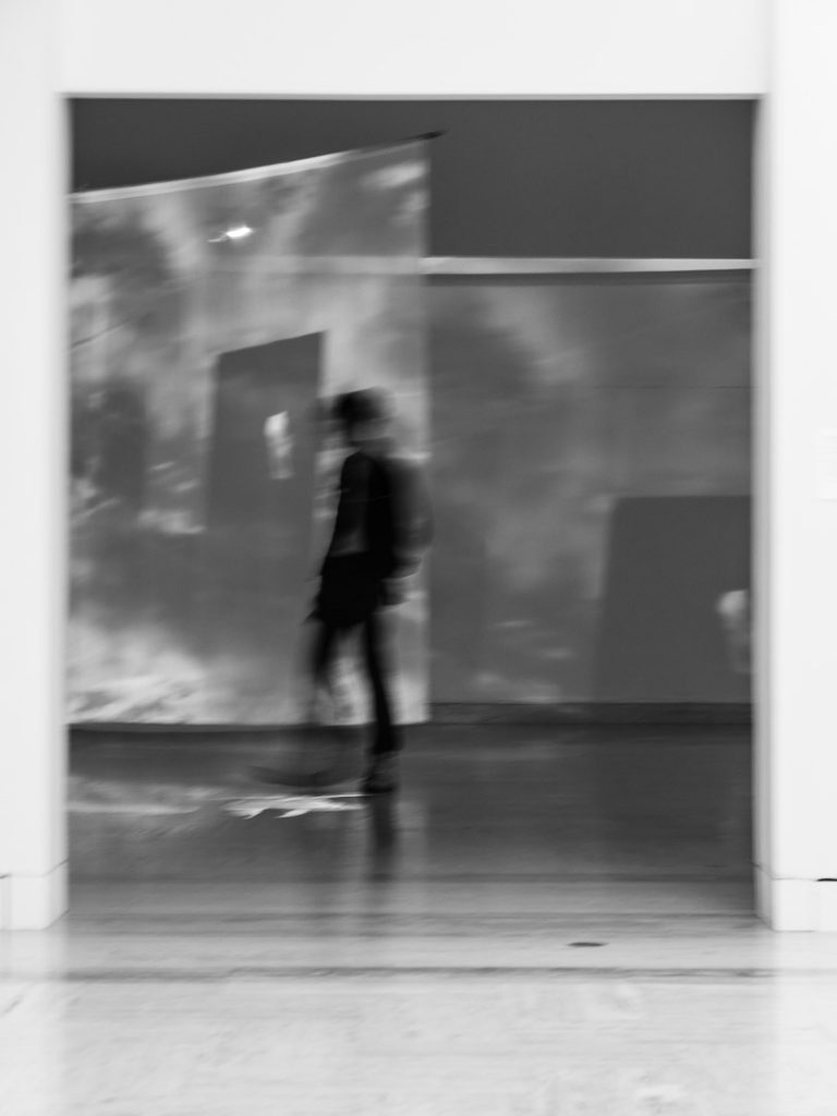 Blurred silhouettes of a man visiting an art museum