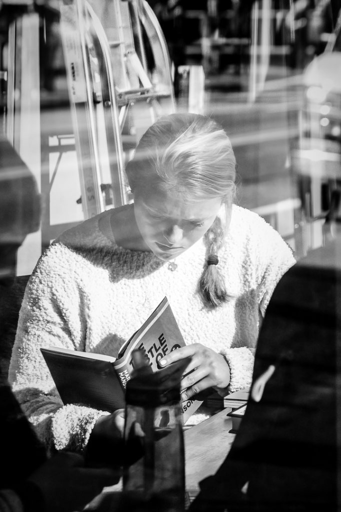 Woman reading a nook in the window of Powells Books Portland