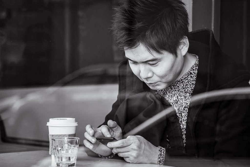 Man typing in a cell phone in the window of a coffee shop