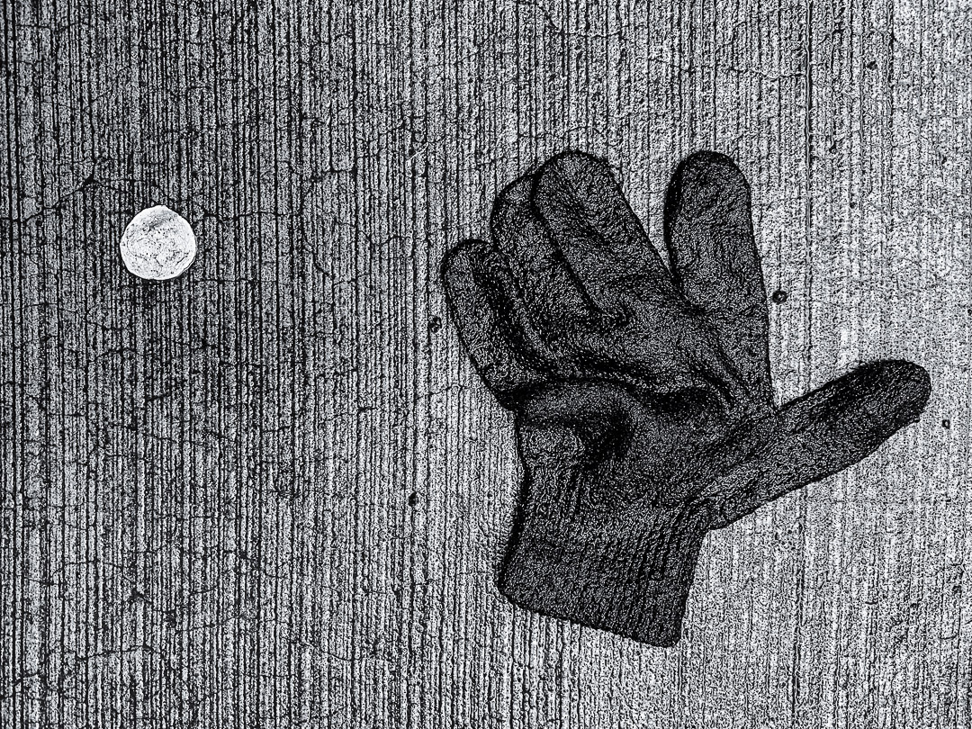 Still Life of a lost glove lying on a wet street