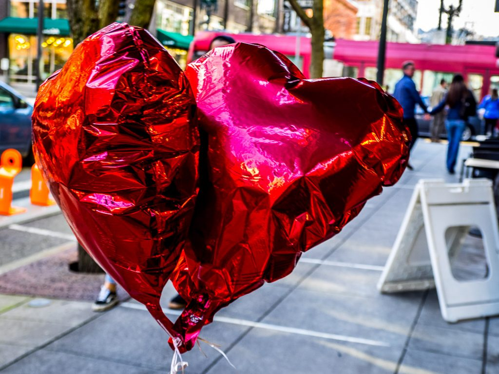 Valentines Hearts balloons and a walking couple holding hands