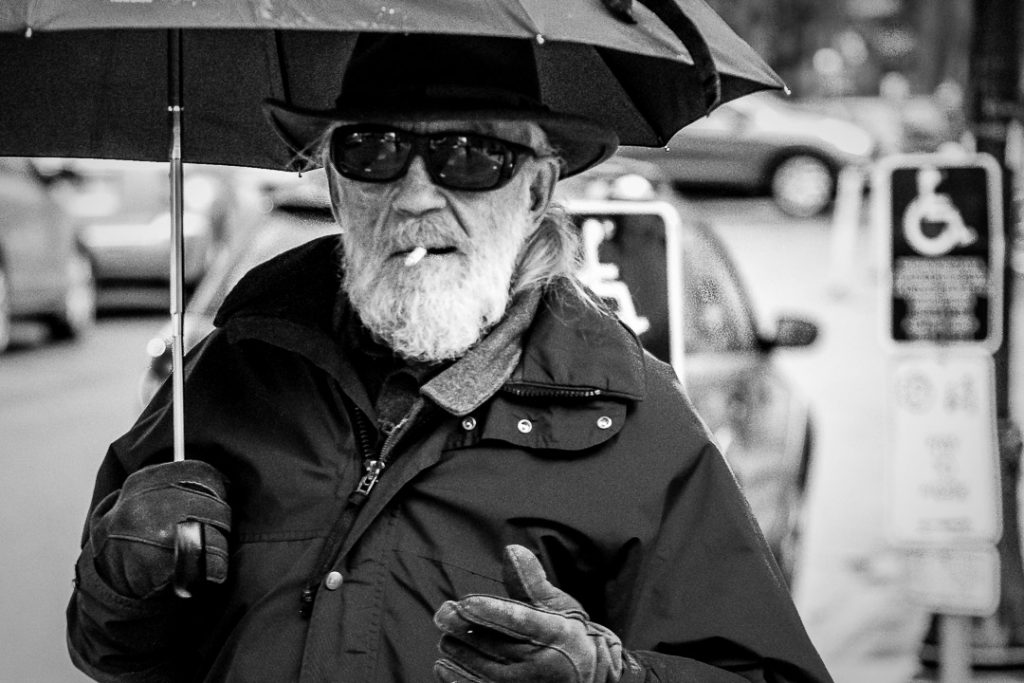 Smoking old Man holding an umbrella and walking through the rain