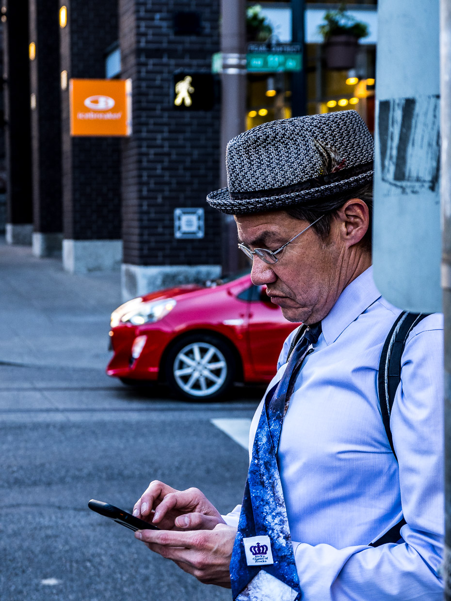 Man with funny hat typing in his phone waiting at a red traffic light