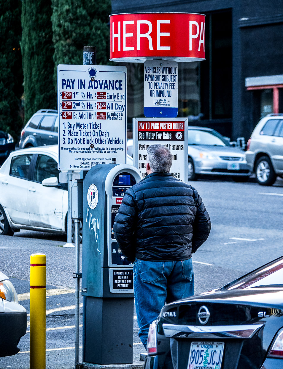 Man standing in front of park meter seemingly lost with the instructions