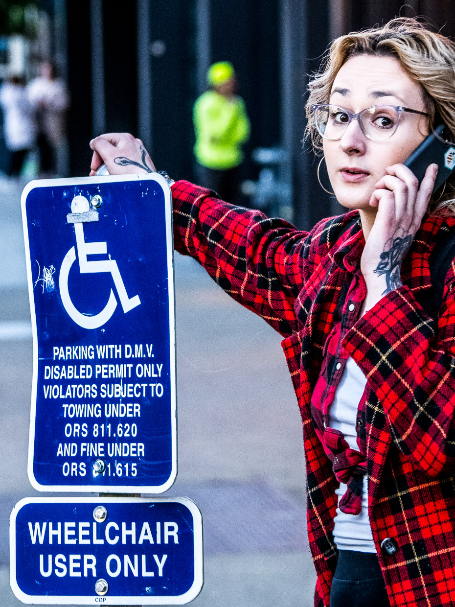 Woman standing leaned on handicapped parking sign talking into phone
