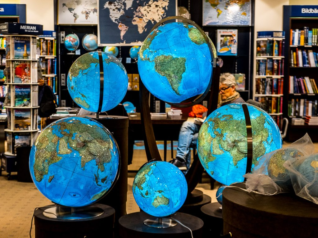 Man sitting behind illuminated globes in a travel book shop