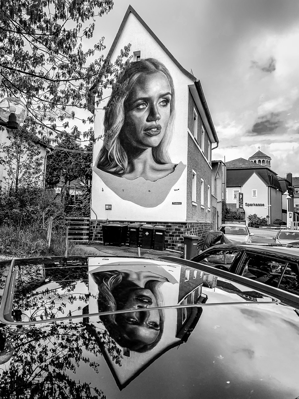 Mural with a woman's face with a reflection in a car roof