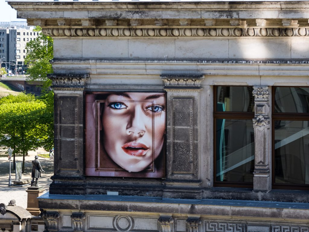 Mural with a woman's face looking out of a historic building in Dresden