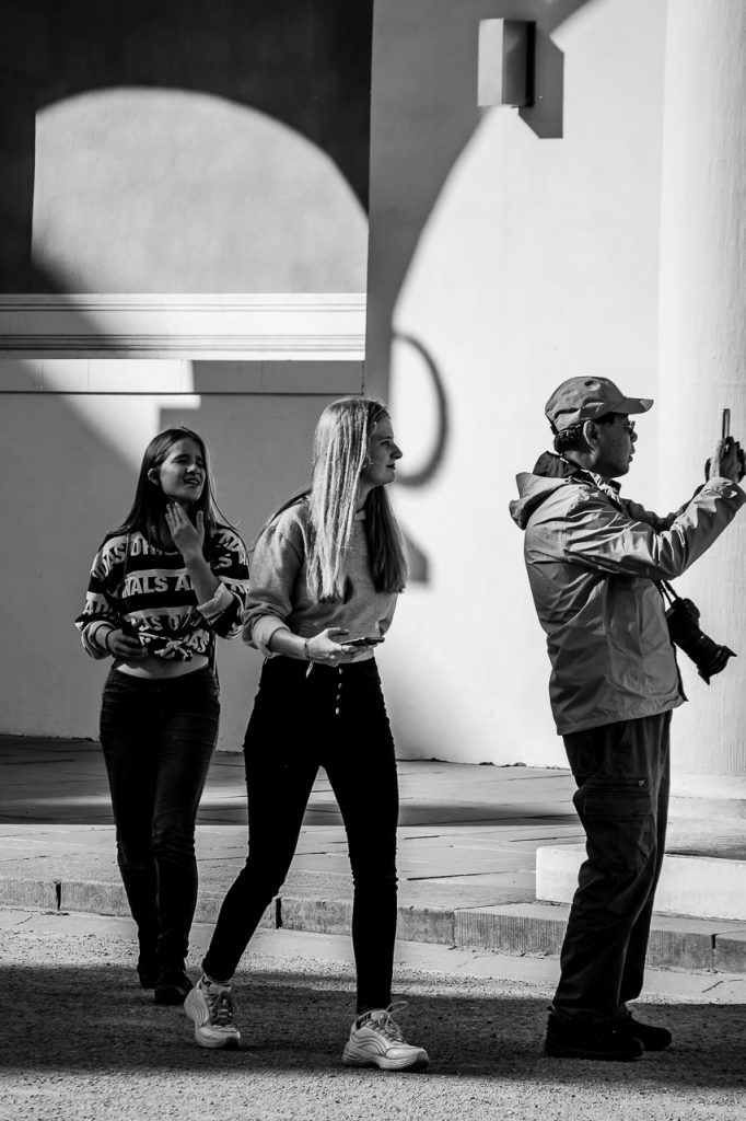 Two young girls checking out a Chinese selfie making tourist
