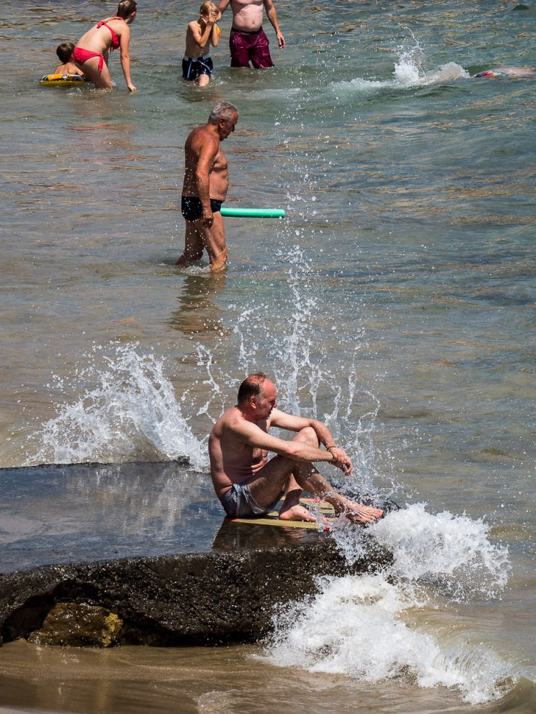 Beach fun, an old man getting a splash