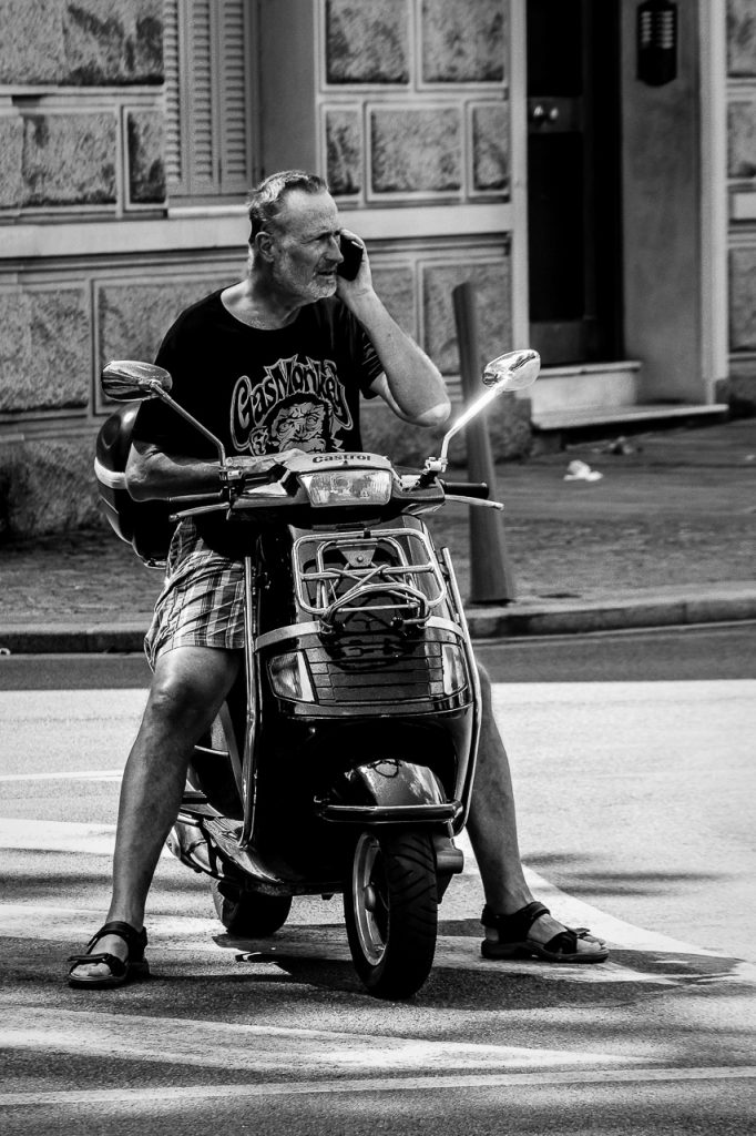 Man sitting on a scooter phoning
