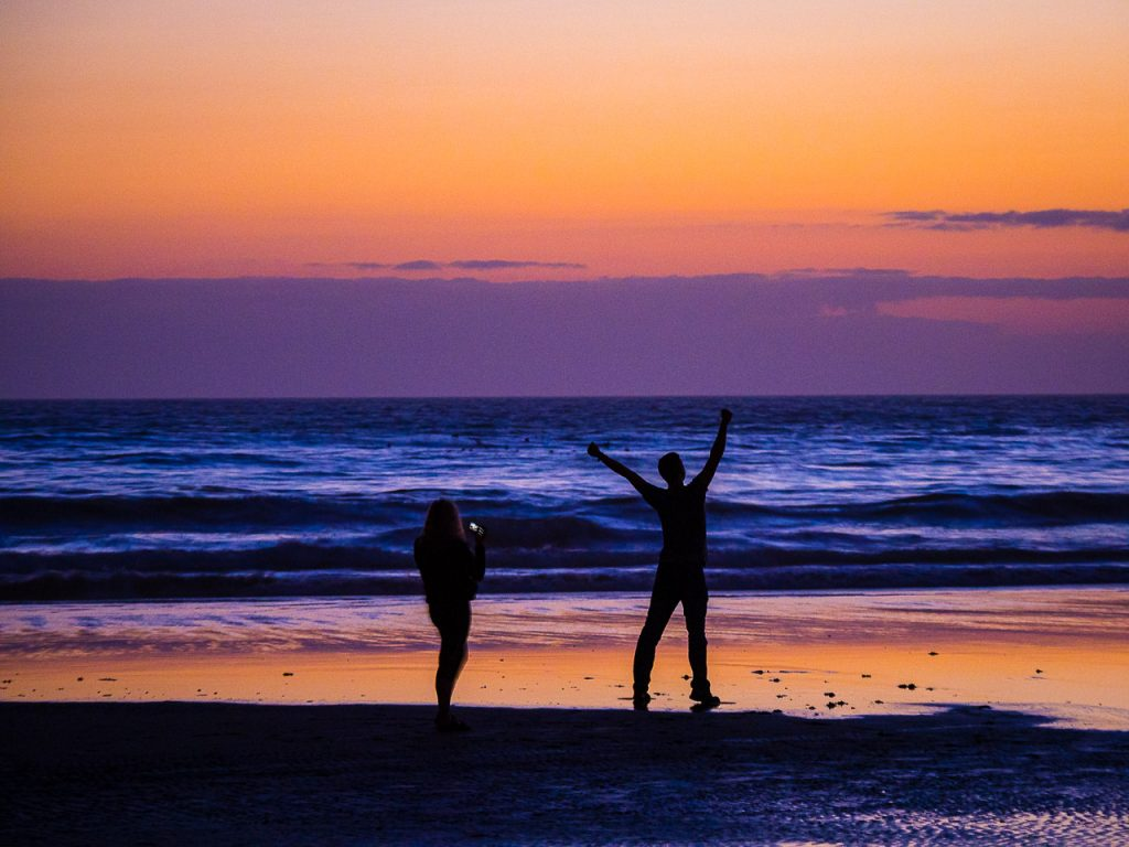 Silhouettes of a photographing couple at a colorful ocean beach