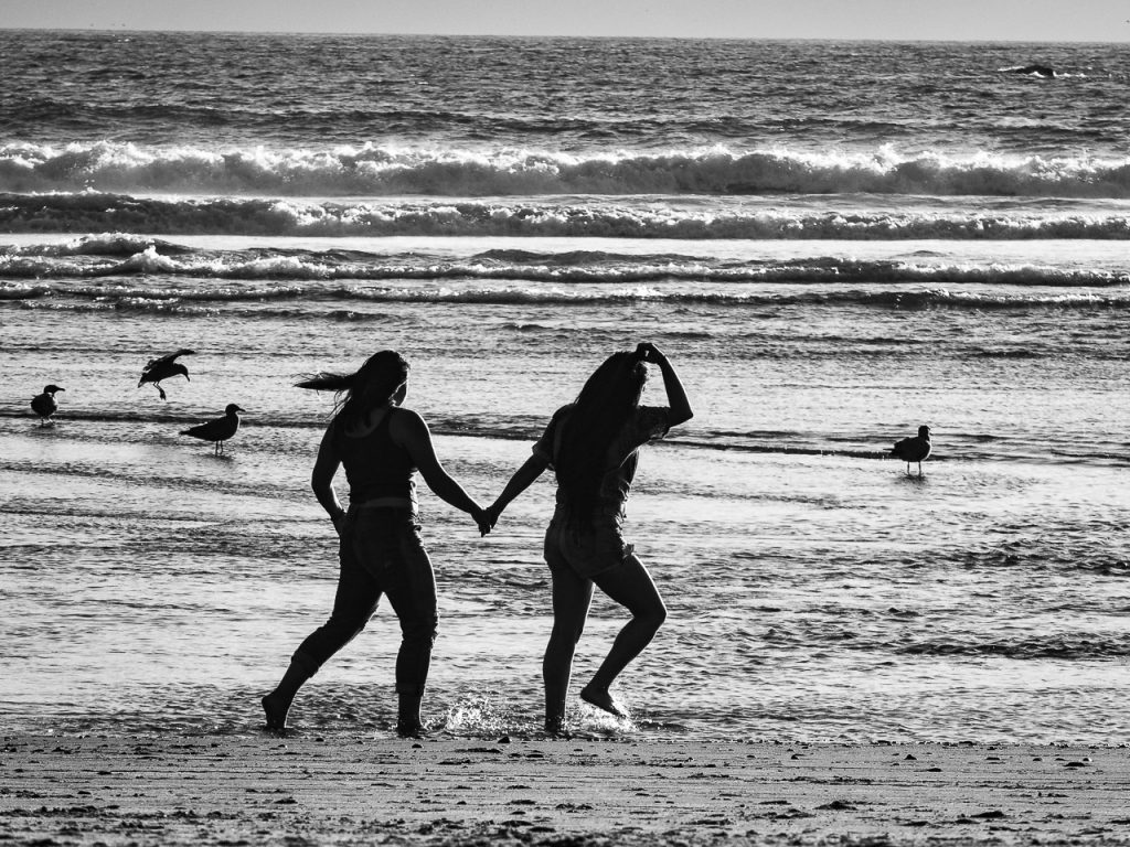 Two teenager girls running hand in hand on the beach