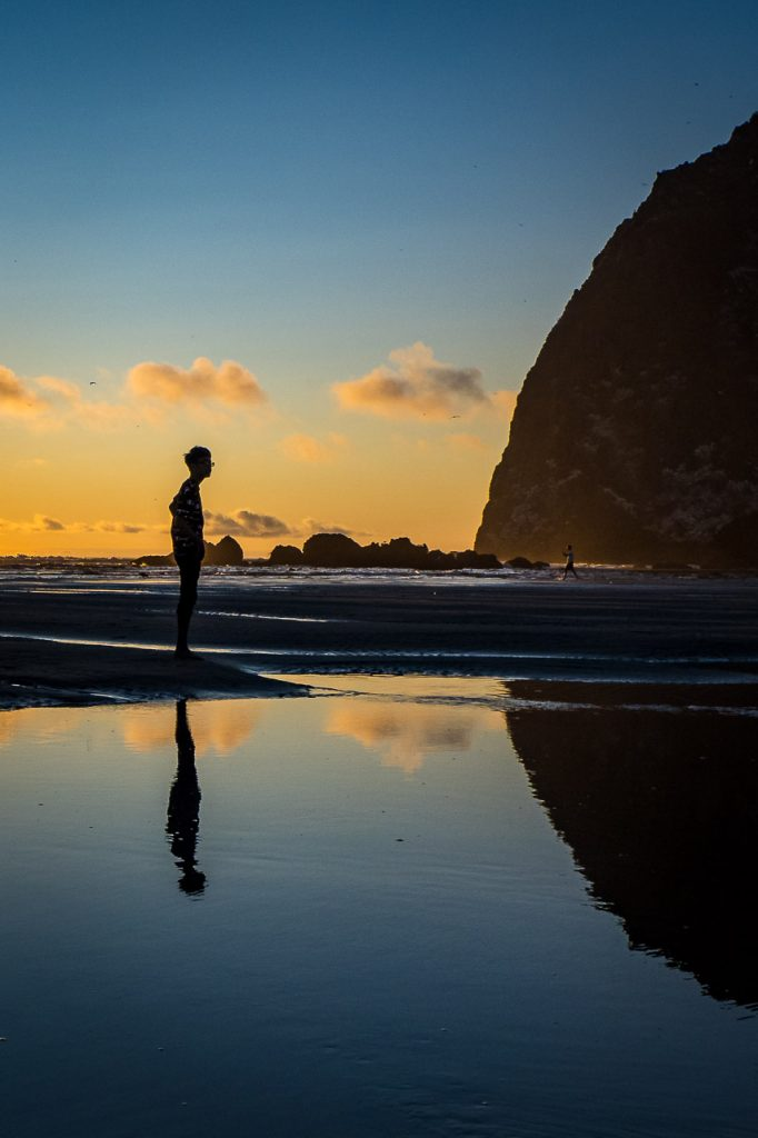 Silhouette of a boy and his reflection looking at Haystack Rock Cannon Beach