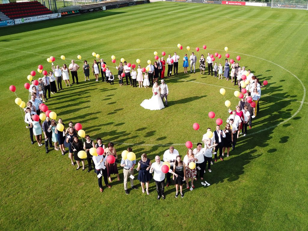 Wedding party standing in a heart photographed from the air