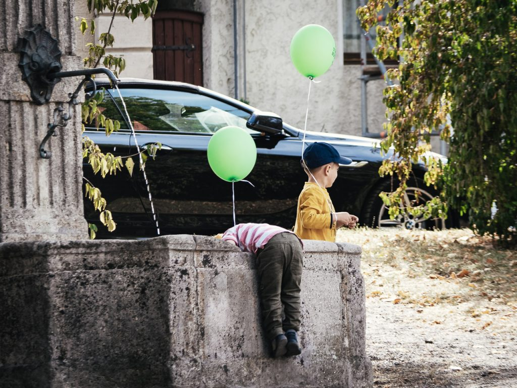 Little boy with a balloon hanging head down over a fountain wall.