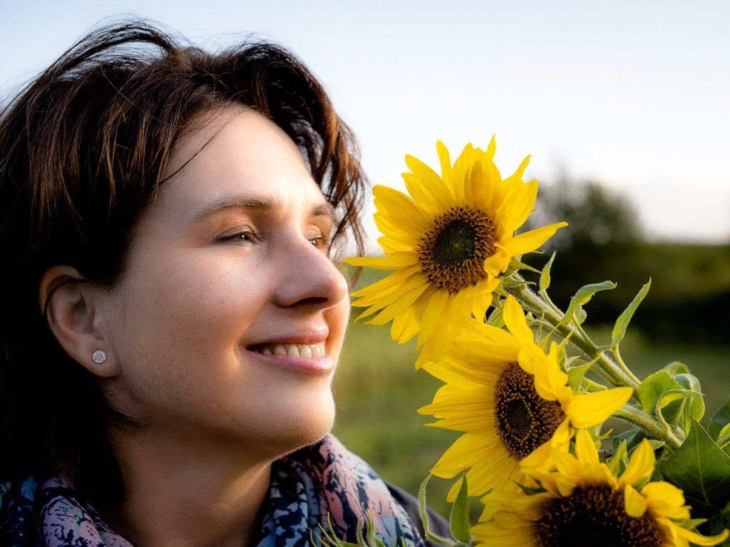 girl in a sunflower field in the golden hour