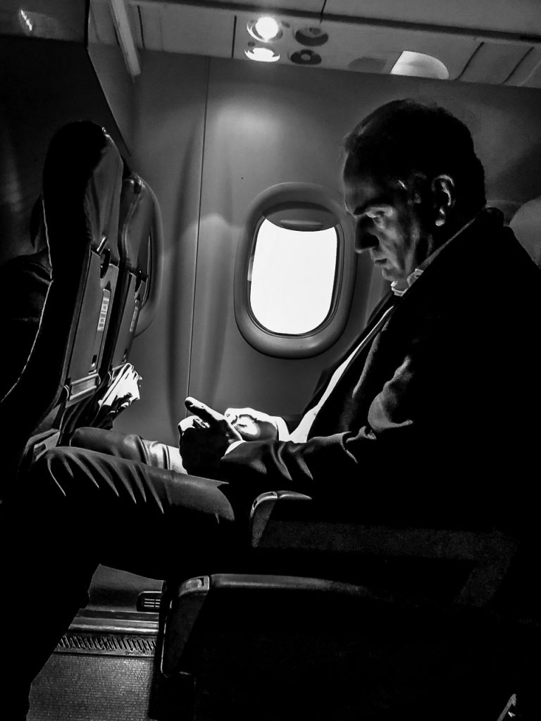 Monochrome street photograph of a passenger in an airliner