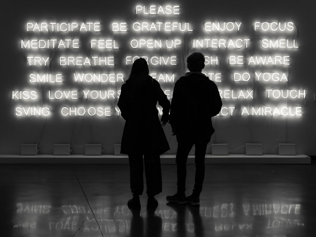 Monochrome street photograph of two people standing in front of an illuminated sign