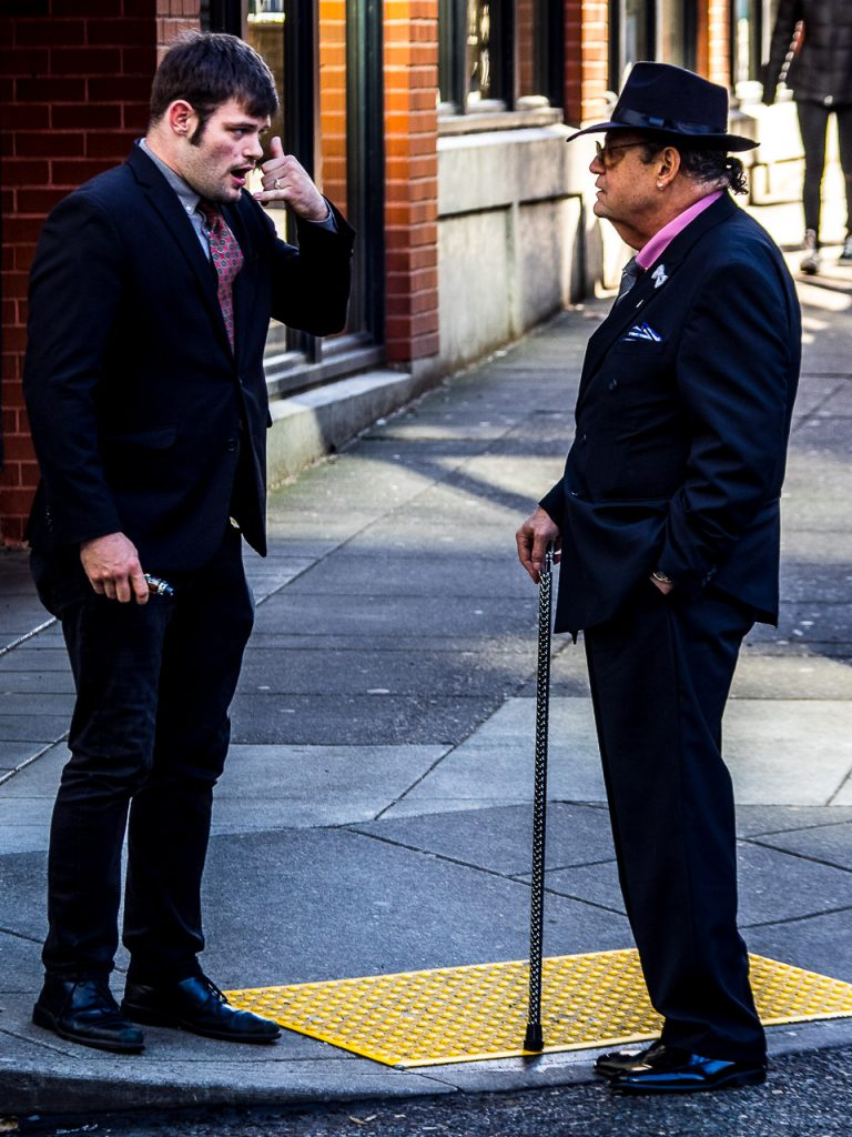 Street photograph of two Mafia type persons talking too each other