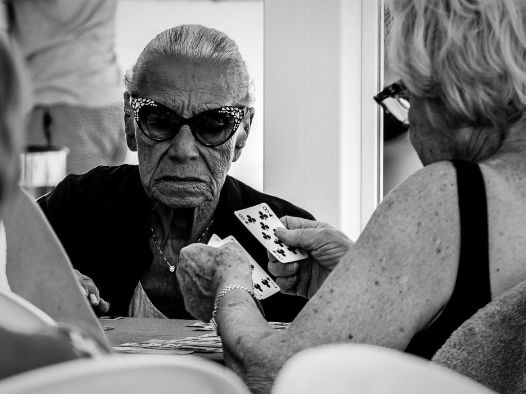 Monochrome street photograph of a lady playing cards