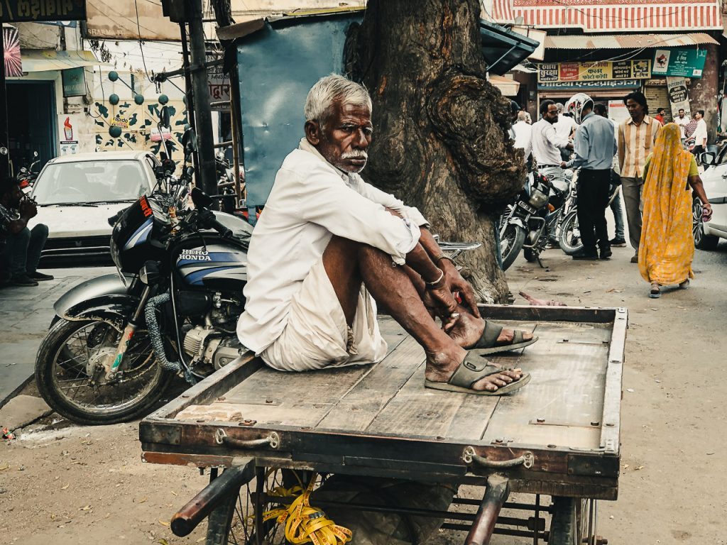 Street photograph of an Indian man sitting on a cart