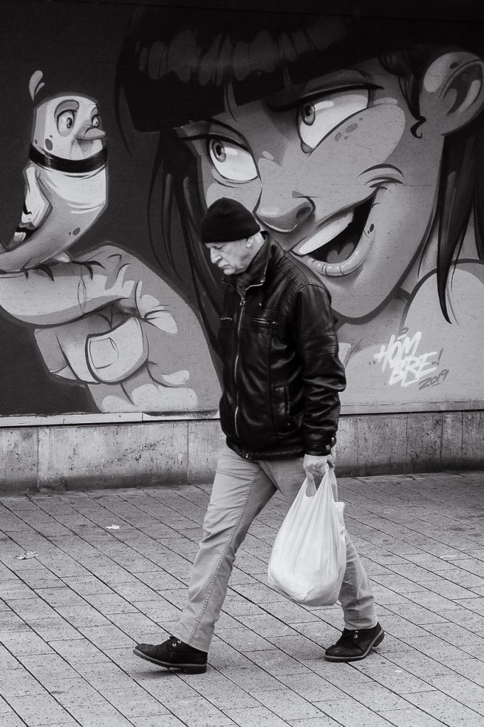 Man walking past a comic mural