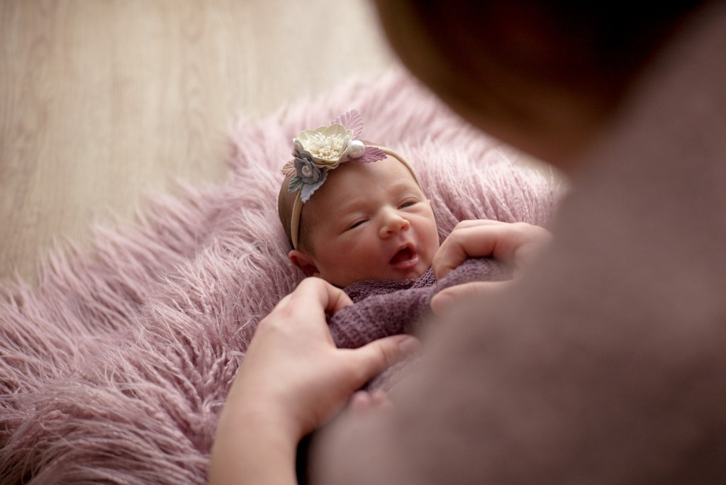 Tiny newborn baby girl with the silhouette of her mother above her