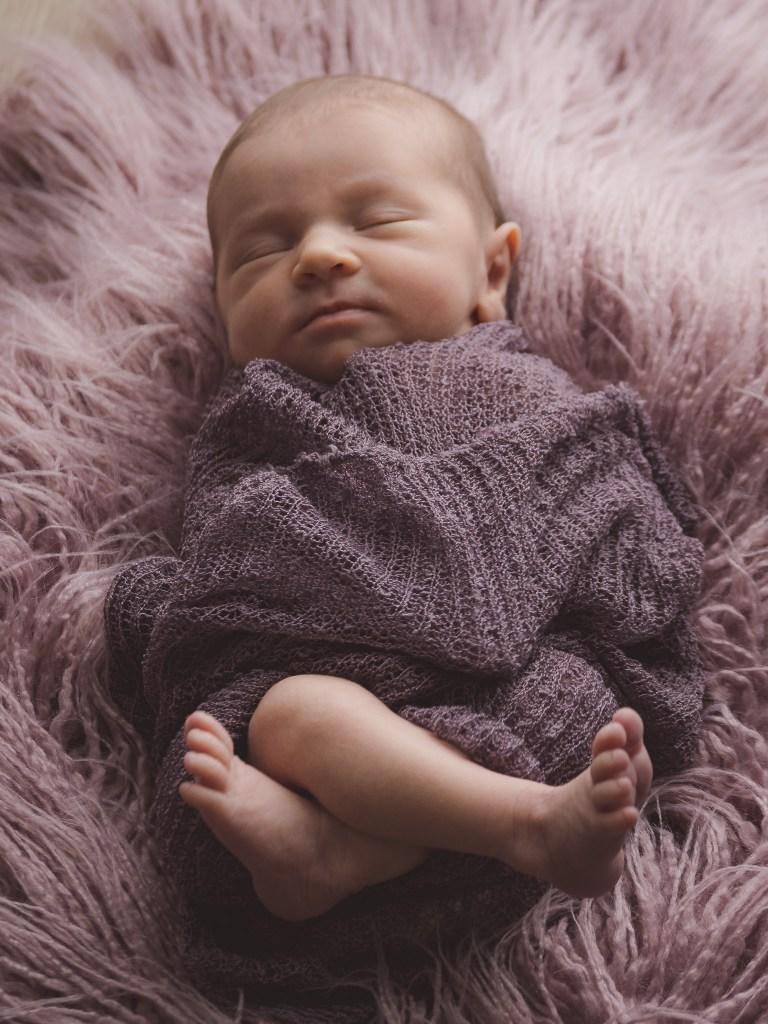 Newborn babygirl cuddled in laying on a fur
