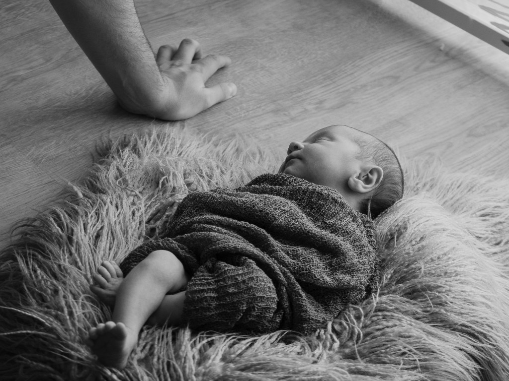 Newborn babygirl cuddled in laying on a fur with the arm of her dad behind