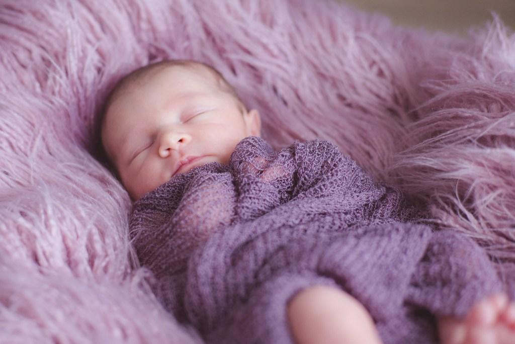 Newborn babygirl cuddled in