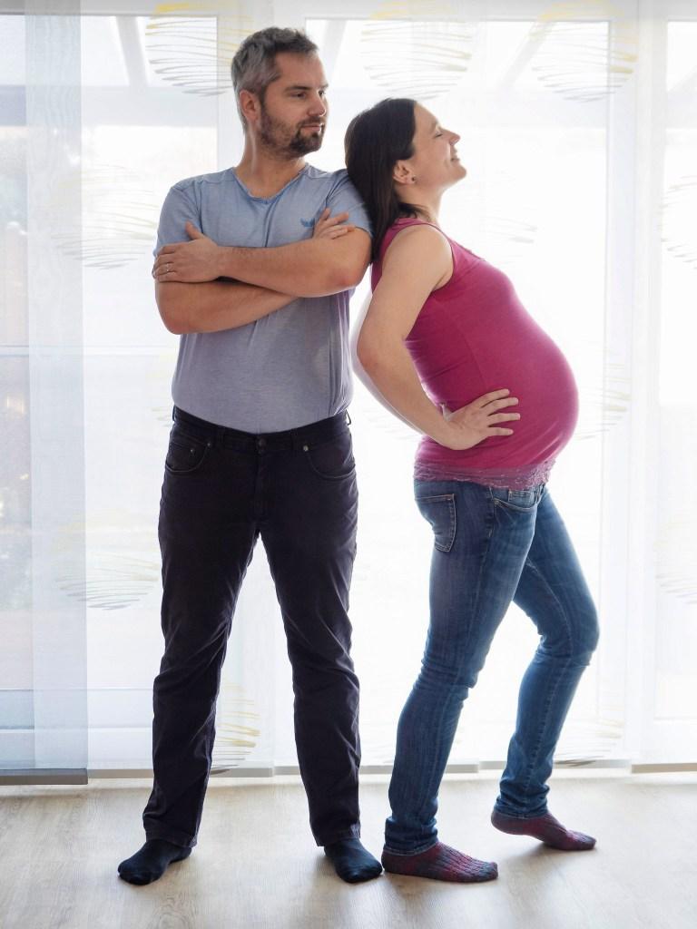 Pregnant Couple standing shoulder to shoulder