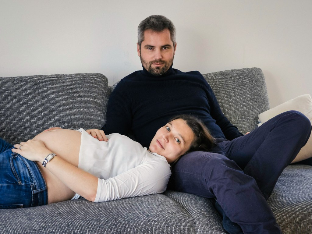 Pregnant couple lounging on their couch