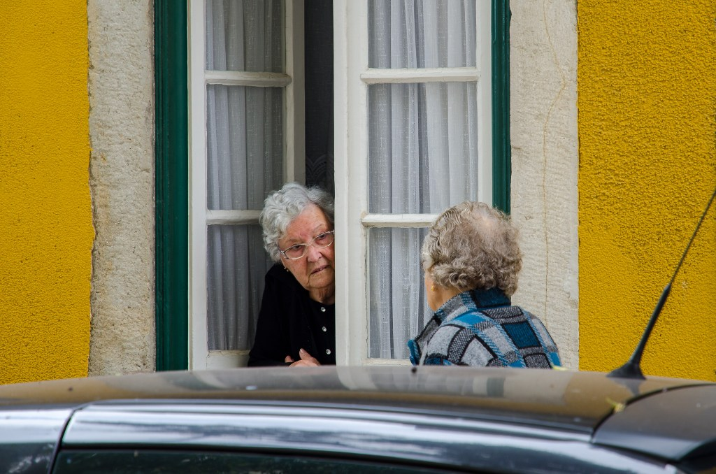 Two elderly ladies talking through a window