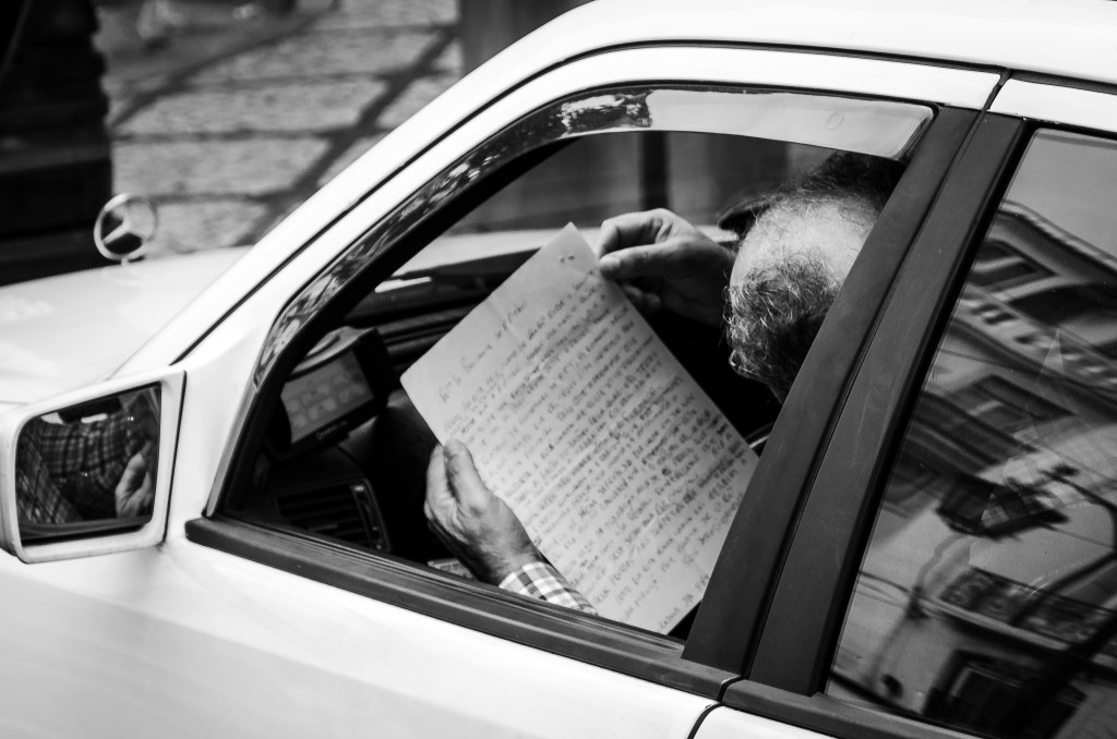 Car driver reading a letter while parked