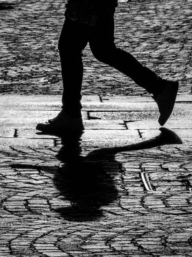 Monochrome street photograph of a man's legs and his shadow