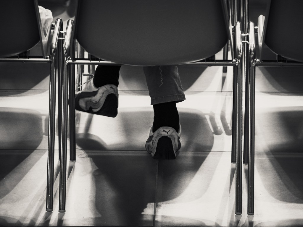 Monochrome street photograph showing the stylish shoes of a man sitting in a chair