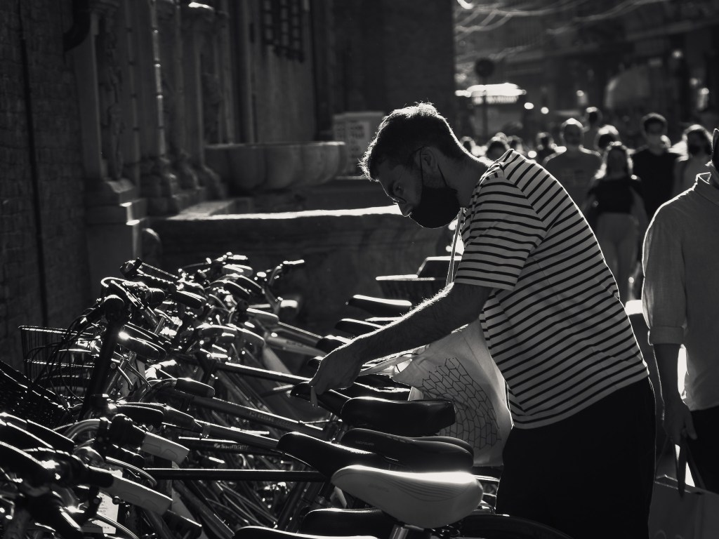 Monochrome street photograph showing the silhouette of a man unlocking his bike