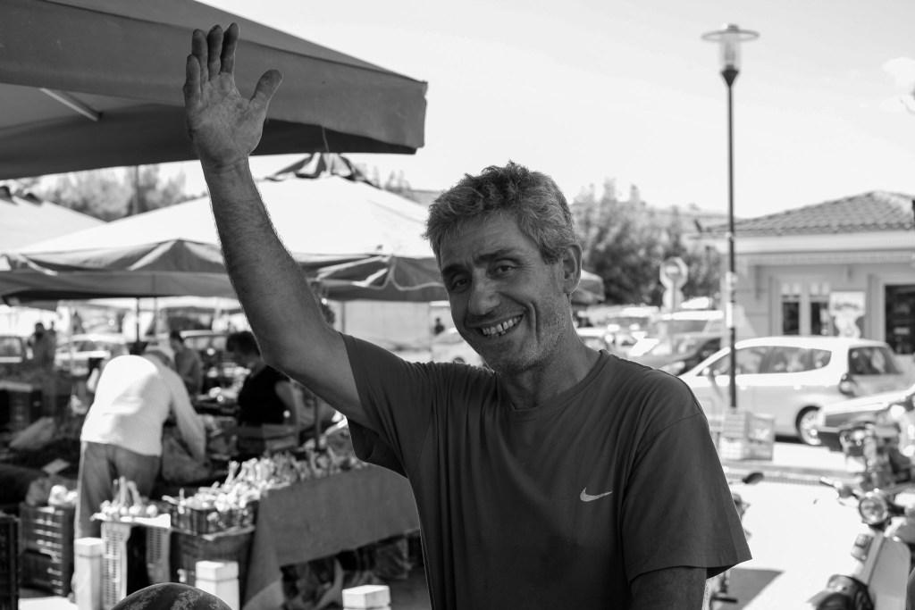 Market vendor waving and smiling at the camera