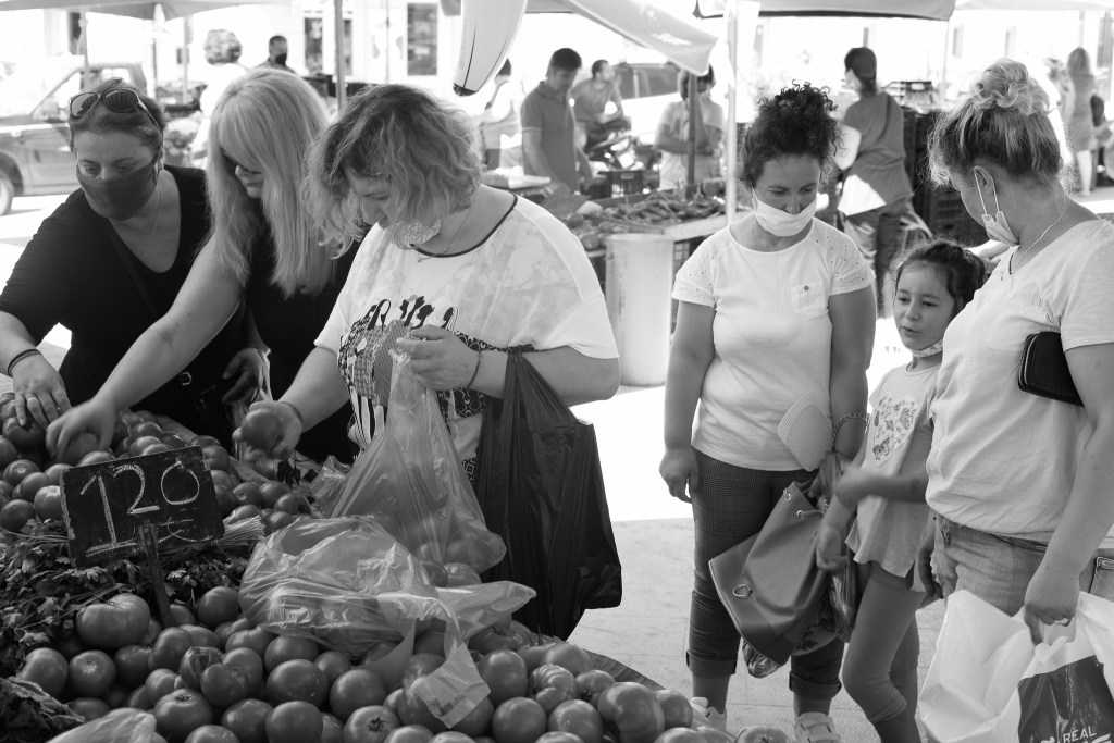 Ladies and a girl buying veggies