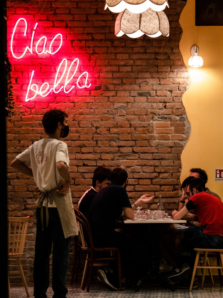 A masked waiter stending under a neon sign reading Ciao Bella