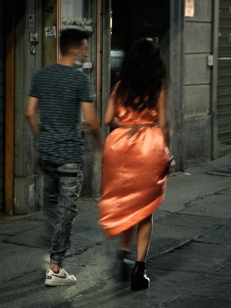 Girl in a fancy dress rushing through an alley