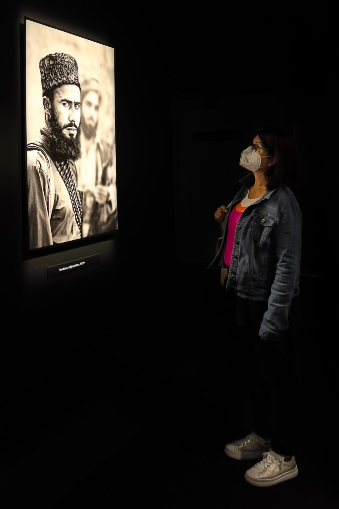 Lady looking at a Steve McCurry Portrait of an Afghan