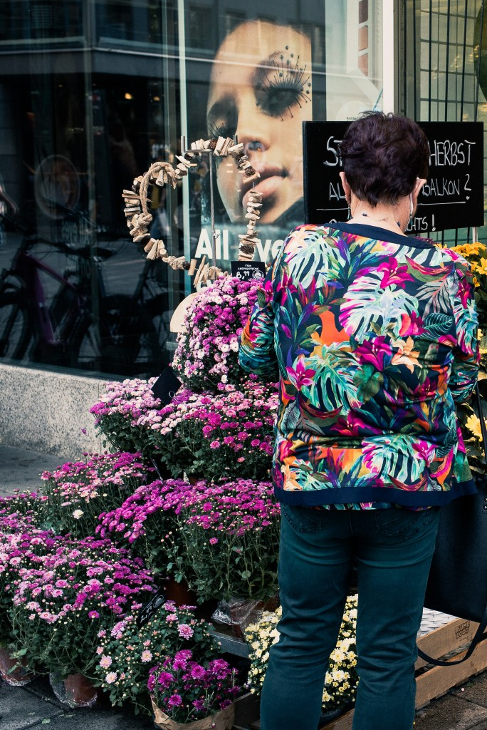 Camouflage, lady with flower shirt standing in front of flowers